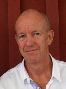 Bild: Porträtt av Ulf Tylestrand iklädd vit skjorta framför en rödmålad brädvägg