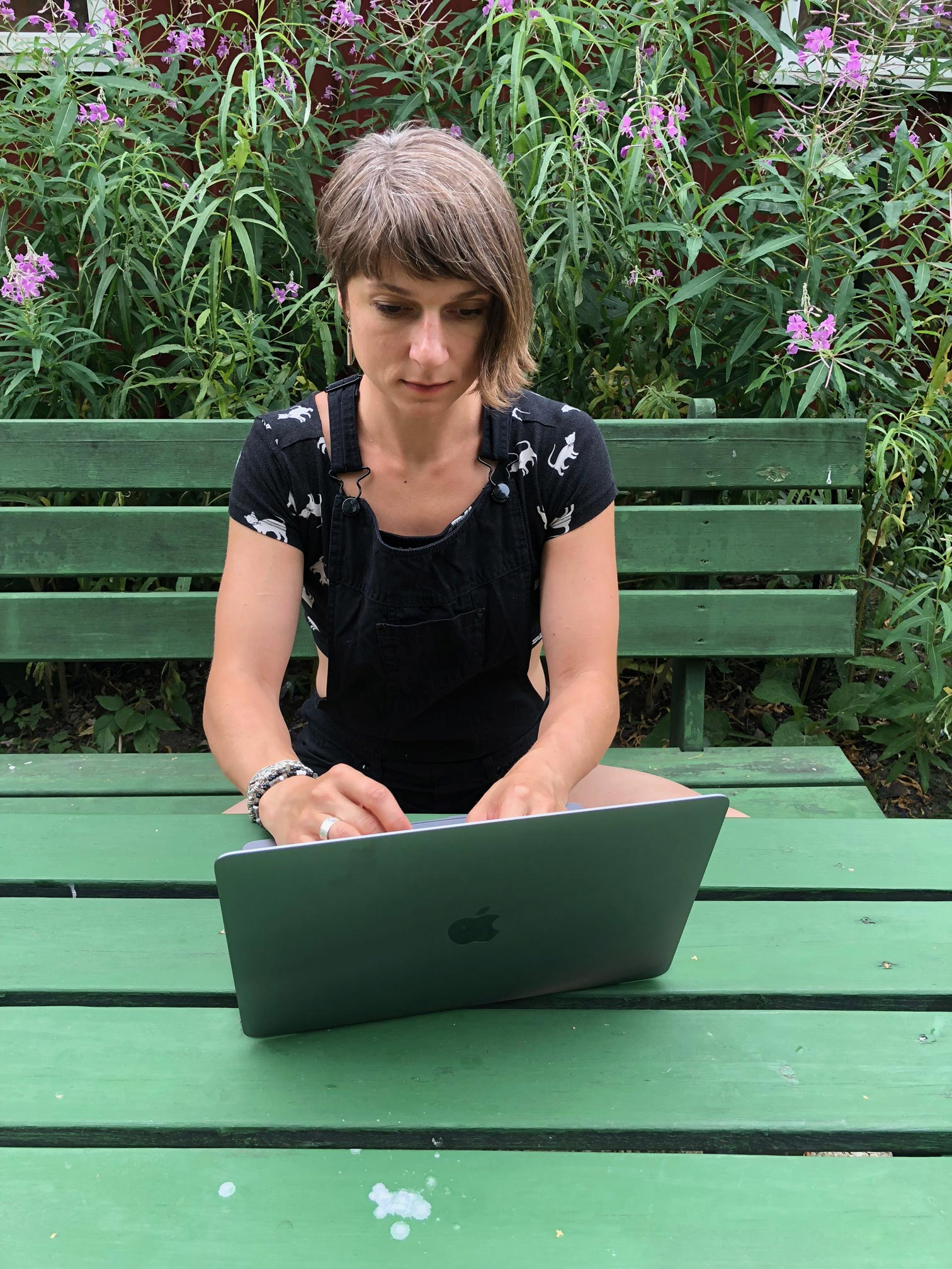 Bild: Anna Nero sitter på en grön bänk vid ett grönt bord och skriver på sin (varumärke). I fonden rikt blommande mjölkört som närmast täcker en faluröd stuga