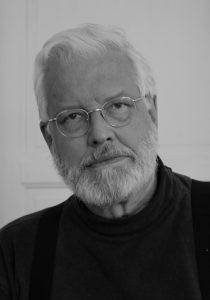 BILD: svartvitt porträtt av Folke T. Olofsson som bär metallbågade glasögon och är iklädd mörk polotröja